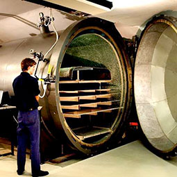 Technician standing next to industrial autoclave